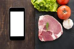 Hoogste menings ruwe varkensvlees en groenten op bord met smartphone royalty-vrije stock foto