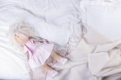 Hoogste meningsbed met verfrommeld bedblad, Goedemorgen na een comfortabele slaap Witte hoofdkussen en deken Doll op het bed exem stock afbeelding