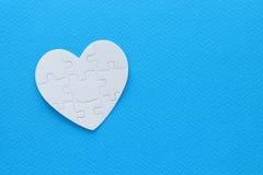 Hoogste meningsbeeld van document hartraadsel over pastelkleurachtergrond stock fotografie