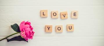 Hoogste meningsbericht I houdt van u spelde in houten blokken met roze pioenbloem op witte houten lijst Liefde, de achtergrond va stock foto