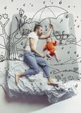 Hoogste meningsfoto van jonge mensenslaap in een groot wit bed en zijn dromen royalty-vrije stock fotografie
