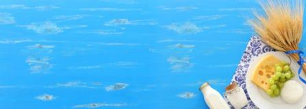 Hoogste meningsfoto van zuivelproducten over blauwe houten achtergrond Symbolen van Joodse vakantie - Shavuot royalty-vrije stock afbeelding