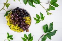 Hoogste meningskom van diverse druiven: rode, witte en zwarte bessen en groene bladeren op de witte houten achtergrond Selectieve Royalty-vrije Stock Afbeeldingen