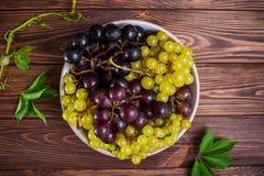 Hoogste meningskom van diverse druiven: rode, witte en zwarte bessen en weinig groene bladeren op de donkere houten achtergrond S Stock Foto's