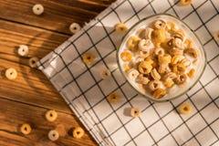 Hoogste meningskop van melk met graangewassenringen in een zonnige ochtend als gezond ontbijt Stock Afbeelding