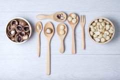 Hoogste meningsmacadamia noten en shell in houten kom en lepels Stock Fotografie