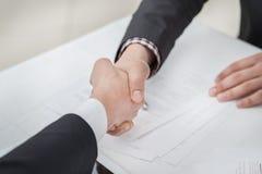 Hoogste overeenkomst! Jonge zakenlieden die handen met elkaar schudden Royalty-vrije Stock Foto