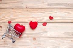 Hoogste rode het hartvorm van het meningspaar met miniboodschappenwagentje op houten lijst liefde, het winkelen en Valentine Day stock afbeeldingen