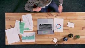 Hoogste schot, tijdtijdspanne twee zakenlieden die bij houten Desktop zitten en met documenten en usinalaptop werken, bureau stock videobeelden