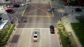 Hoogste Weergeven van straat met kruisingsweg en mensen die de straat kruisen bij nacht schot Satellietbeeld van stadskruispunt stock video