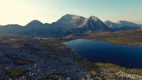Hoogte in de berg, het meer en de pieken stock videobeelden