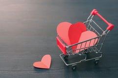 Hoogtepunt van harten in het boodschappenwagentje op houten vloer Royalty-vrije Stock Fotografie