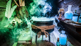 Hoogtepunt van magisch mengsel in heksenhut met boeken en blauwe drankjes voor Halloween Stock Foto's