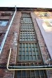 hooimijtmuur van woningbouw met vensters en rioolbuis, mening van grond stock foto's