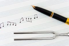 Hooivork en pen op muziekblad Royalty-vrije Stock Fotografie