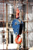 A  hook of a crane. A blue-orange crane hook with a scaffolding  construction background Stock Photo
