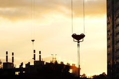 Hook of crane on background of silhouettes of buildings Stock Photo