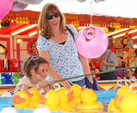 Hook the duck fun fair. Photo of young girl having fun trying to hook the duck at whitstable fun fair in kent on 17th may 2014.photo ideal for fun fairs,leisure royalty free stock photography