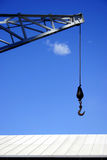 Hook and roof. Crane hook over blue sky and roof Royalty Free Stock Photography