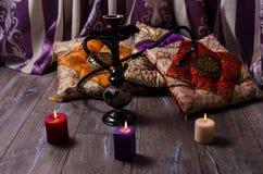 Hookah σε ένα υπόβαθρο των ασιατικών μαξιλαριών και των κεριών Στοκ εικόνα με δικαίωμα ελεύθερης χρήσης