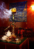 Hookah. With white smoke and tea cups on a table Stock Photos