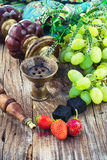 Hookah amid bunches of grapes and strawberries Royalty Free Stock Photos