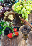 Hookah amid bunches of grapes and strawberries Stock Photo