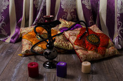 Hookah on a background of oriental cushions and candles Royalty Free Stock Image