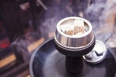 Hookah with burning coals is on the table. Hookah with burning coals is on the table and all in the smoke Royalty Free Stock Photo