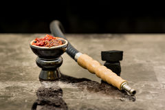 Hookah head, pipe, tobacco, and coals on the table. Hookah head with tobacco inside and pipe and coals on the table with black background Royalty Free Stock Photos