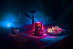 Hookah hot coals on shisha bowl making clouds of steam at Arabian interior. Oriental ornament on the carpet eastern tea ceremony. Stock Photo