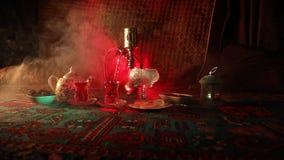Hookah hot coals on shisha bowl making clouds of steam at Arabian interior. Oriental ornament on the carpet eastern tea ceremony. Hookah hot coals on shisha stock video