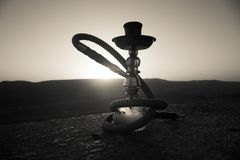 Hookah, traditional arabic waterpipe, direct sunset light, outdoor photo. Mountain background or Silhouettes of hookah on sunset b. Ackground. Outdoor. Selective royalty free stock images