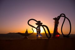 Hookah, traditional arabic waterpipe, direct sunset light, outdoor photo. Mountain background or Silhouettes of hookah on sunset b. Ackground. Outdoor. Selective stock image