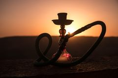 Hookah, traditional arabic waterpipe, direct sunset light, outdoor photo. Mountain background or Silhouettes of hookah on sunset b. Ackground. Outdoor. Selective stock photography