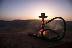 Hookah, traditional arabic waterpipe, direct sunset light, outdoor photo. Mountain background or Silhouettes of hookah on sunset b. Ackground. Outdoor. Selective stock photos