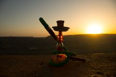 Hookah, traditional arabic waterpipe, direct sunset light, outdoor photo. Mountain background or Silhouettes of hookah on sunset b. Ackground. Outdoor. Selective royalty free stock photo