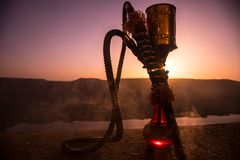 Hookah, traditional arabic waterpipe, direct sunset light, outdoor photo. Mountain background or Silhouettes of hookah on sunset b. Ackground. Outdoor. Selective royalty free stock photography