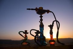 Hookah, traditional arabic waterpipe, direct sunset light, outdoor photo. Mountain background or Silhouettes of hookah on sunset b. Ackground. Outdoor. Selective royalty free stock image