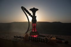 Hookah, traditional arabic waterpipe, direct sunset light, outdoor photo. Mountain background or Silhouettes of hookah on sunset b. Ackground. Outdoor. Selective royalty free stock photos