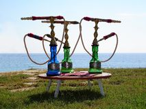 Hookahs on small table. Three colorfull glass hookahs on small table. Borderless sea behind. Clear blue sky royalty free stock photos