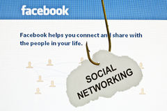 Hooked on Facebook. Rousse, Bulgaria - June 16, 2011: Close up of a hooked paper with printed 'SOCIAL NETWORKING' on it, infront of Facebook's main page royalty free stock photo