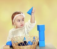 Hooked little girl playing with pyramid. Royalty Free Stock Photography
