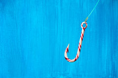 Hooked on sugar. Hook-shaped candy cane with fishing line over b. Lue painted background stock image