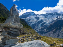 Hooker Valley rock cairn Aoraki Mt Cook trail NZ. Rock cairn in Hooker Valley on a trail leading to Aoraki, Mount Cook, highest peak of Southern Alps an icon of Royalty Free Stock Images
