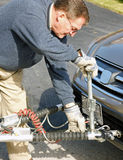Hooking Up a Towing Hitch. A senior making preparations to hit the road with his motor home and car in tow Royalty Free Stock Image