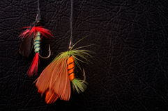 Hooks. Two fishhooks ,isolated on black  leather  background Stock Photo