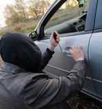 Hooligan breaking into car Stock Photos