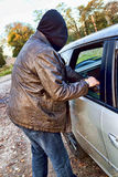 Hooligan breaking into car Royalty Free Stock Photo