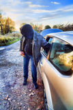 Hooligan breaking into car Royalty Free Stock Image